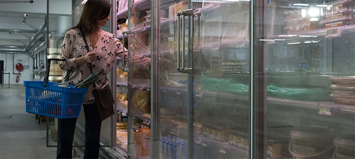 Lady choosing food from supermarket refrigerator