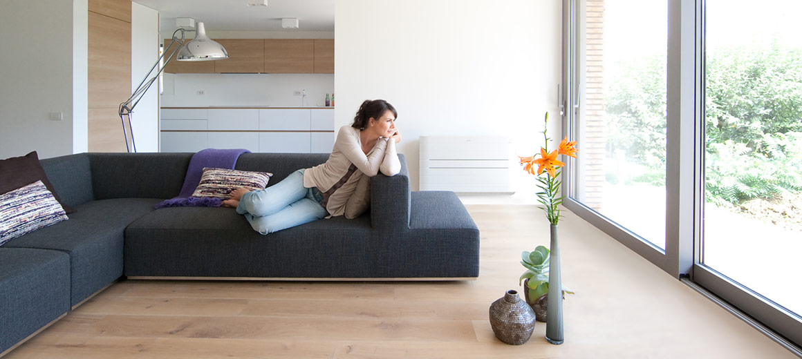 Lady laying on sofa in comfortably heated room